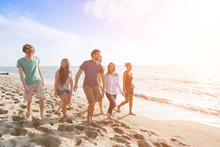 Multiracial Group Of Friends Walking At Beach