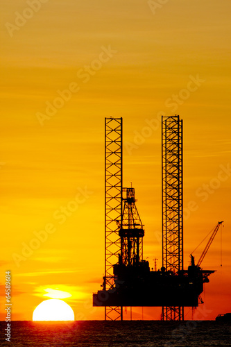 Silhouette of an offshore drilling rig at sunset - Buy this