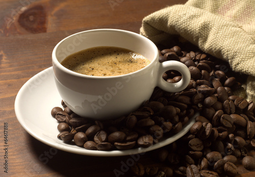 Foto op Canvas Cafe coffee cup and grains on wooden table