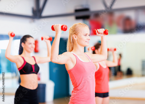 group of smiling women working out with dumbbells
