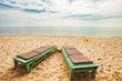 Wooden chairs on sand beach
