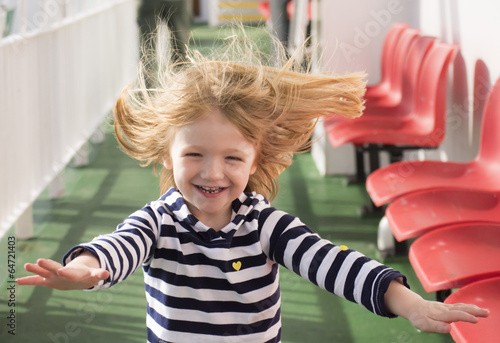 Valokuva  Little blonde girl running with windswept hair