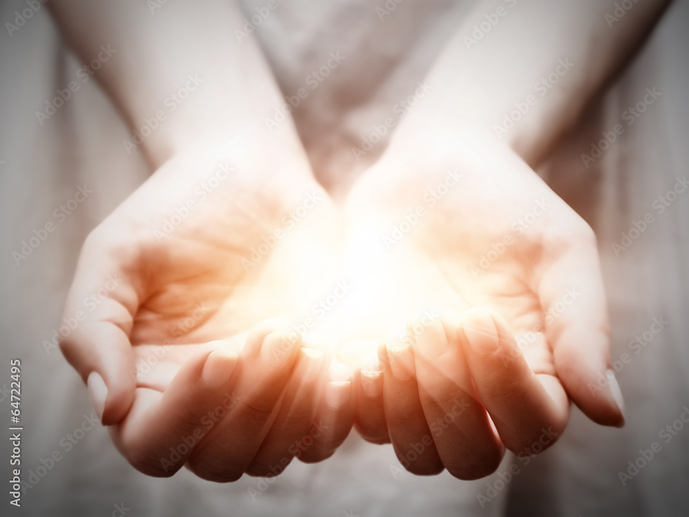 Fototapeta The light in young woman hands. Sharing, giving, protection