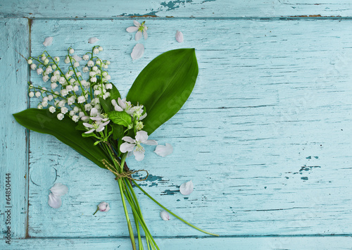 In de dag Lelietje van dalen Lovely bouquet of lilies of the valley on a blue wooden table