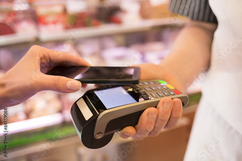 Fotografía  Woman paying with NFC technology on mobile phone, in supermarket
