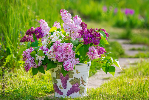 Tuinposter Lilac Beautiful bouquet of lilac in the decoupage decorated bucket