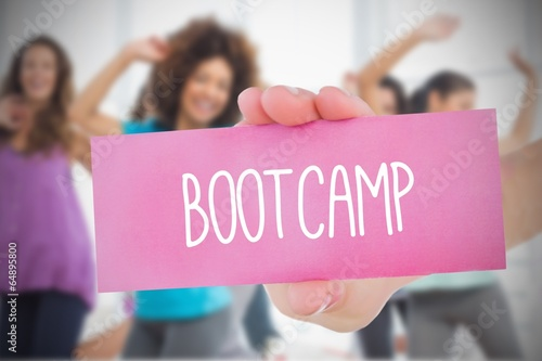 Fotografie, Obraz  Woman holding pink card saying bootcamp
