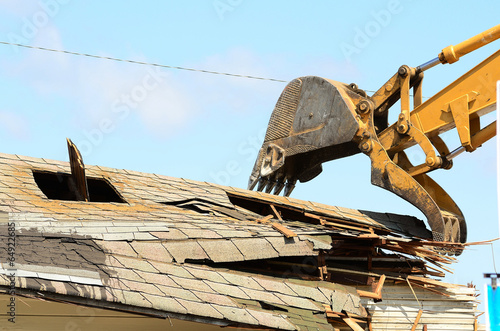 Photo A large track hoe excavator tearing down an old hotel to make wa