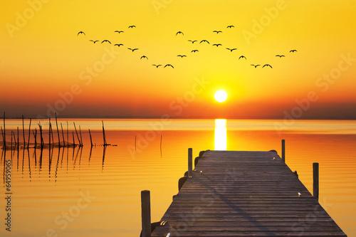 Tuinposter Pier amanece un dia dorado en el mar