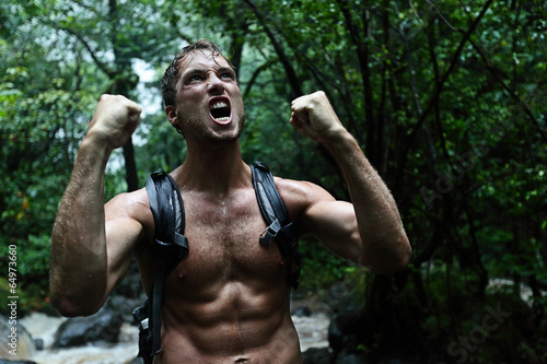 Muscular survivor man in jungle rainforest Canvas Print