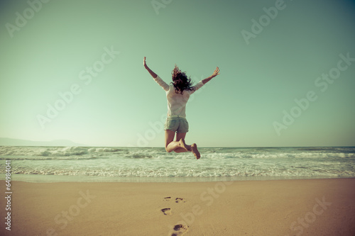 Fotografía  Happy woman jumping at the beach
