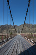 Steel suspension bridge on the background of blue sky.