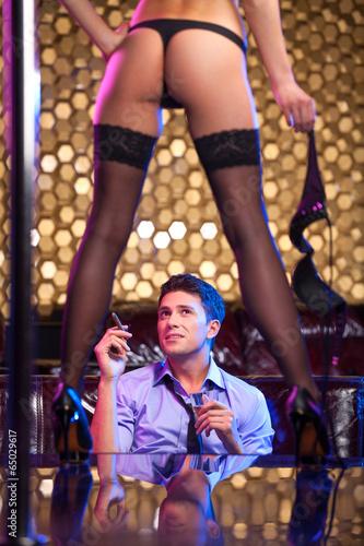 Fotografie, Obraz  Handsome man watching striptease dance.