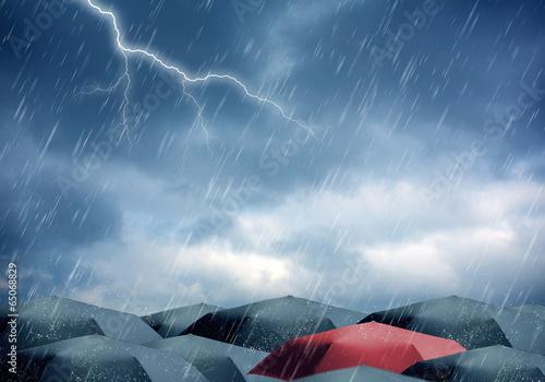 Umbrellas under rain and thunderstorm