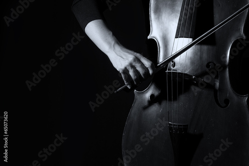 Vászonkép Beautiful woman holding a cello with selective light and black d