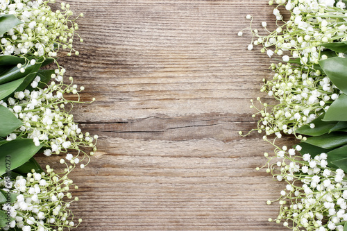Lily of the valley flowers on wooden background.