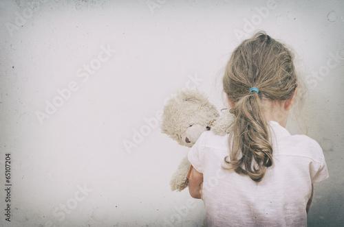 Fototapeta Little girl crying in the corner. Domestic violence concept.