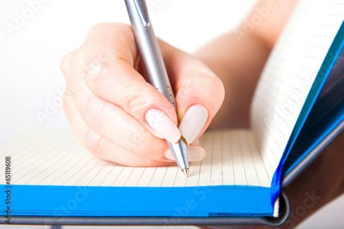 Fototapeta Female hand writing in a notebook obraz na płótnie