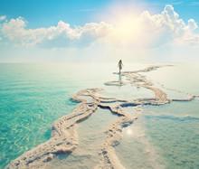 Silhouette Of  Woman Walking On Dead Sea Shore Towards The Sun