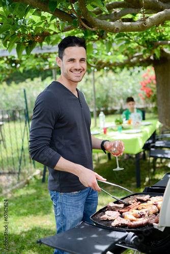 Papiers peints Grill, Barbecue handsome young man cooking barbecue party in garden