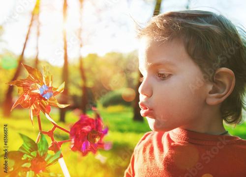 Fotografia, Obraz  Portrait of a cute boy blowing wind wheel in sunshine