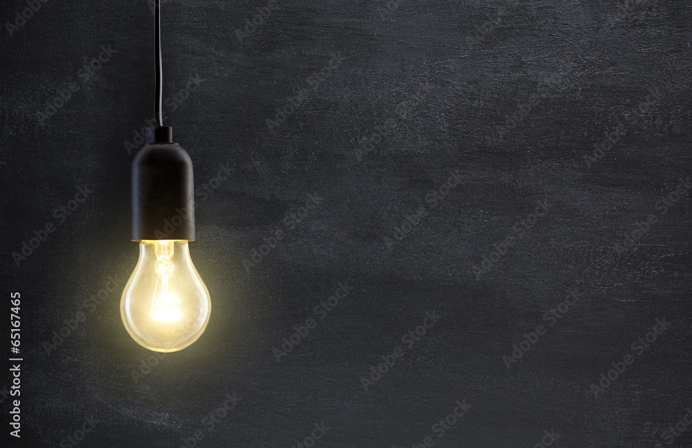 Photo  Light bulb lamp on blackboard background with copy space