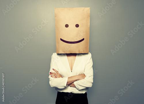 Fotografía  woman hiding under smiley paper bag