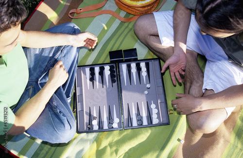 Tableau sur Toile Zwei junge Männer spielen Backgammon,im Freien