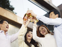 Asian Young Adult Friends Raising Beer Bottles For A Toast
