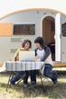 Deutschland,Leipzig,Ammelshainer See,Junges Paar sitzt mit Campingwagen mit Laptop