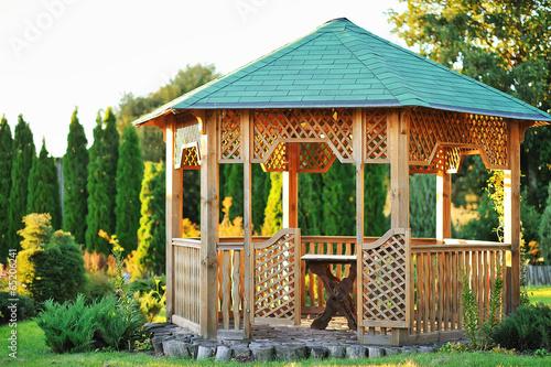 Fototapeta Outdoor wooden gazebo over summer landscape background