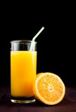full glass of orange juice with straw near half orange