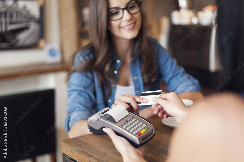 Fototapeta Smiling woman paying for coffee by credit card