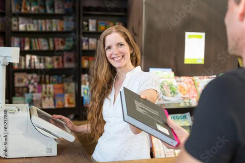 Kassiererin in einer Buchhandlung verkauft Buch einem Kunden Poster Mural XXL