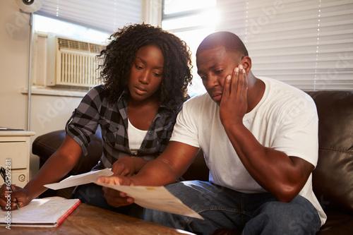 Fotomural  Preocupado pareja de jóvenes sentados en el sofá que mira cuentas