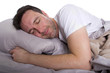 man in bedroom sleeping in on his day off