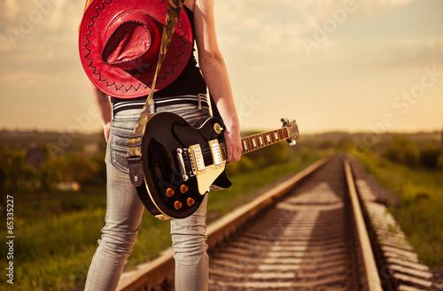 kobieta-z-gitara-na-drodze-kolejowej