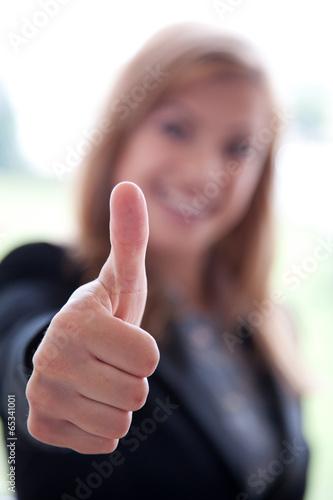 Photographie  Junge Geschäftsfrau zeigt motiviert Daumen hoch
