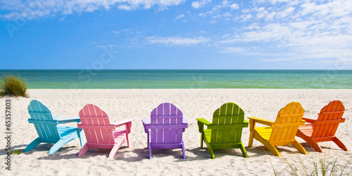 Fotografija Adirondack Beach Chairs on a Sun Beach in front of a Holiday Vac