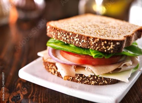 Photo Stands Snack cold cut turkey sandwich on whole wheat with swiss cheese