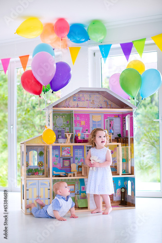Photo  Baby brother and sister playing with a doll house