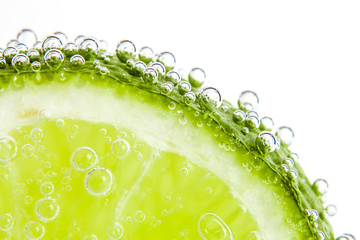 Fototapetaslice of lime in the water with bubbles