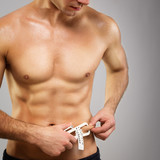 Fit muscular shirtless man with caliper