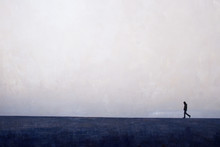 Man Walking  Alone On The Horizon Line