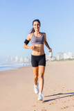 healthy young woman running on beach