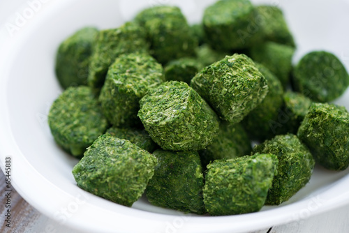 Close-up of a glass plate with spinach cubes, horizontal shot