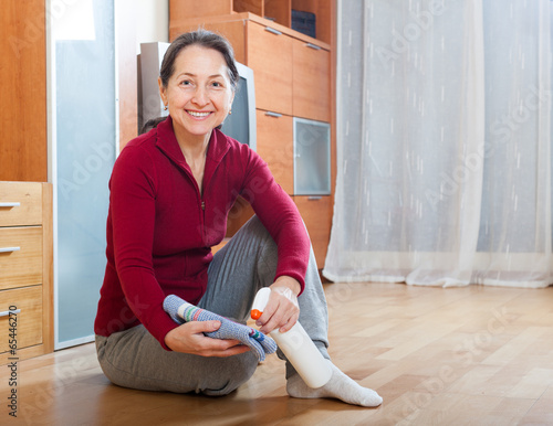 Poster Ecole de Yoga mature woman rubbing wooden floor with rag and cleanser