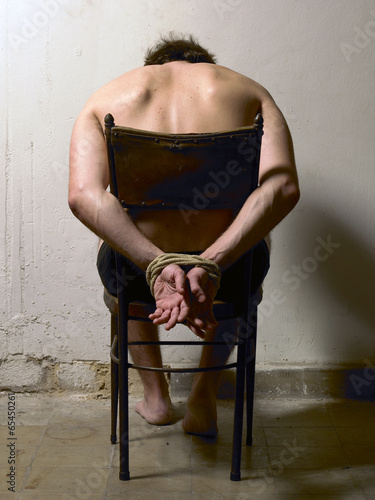 Tortured man on a chair with tied hands Fototapeta