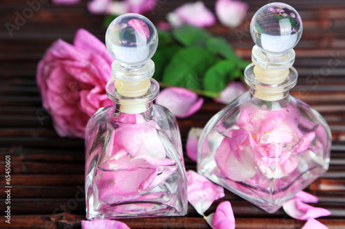 Rose oil in bottles on bamboo mat background