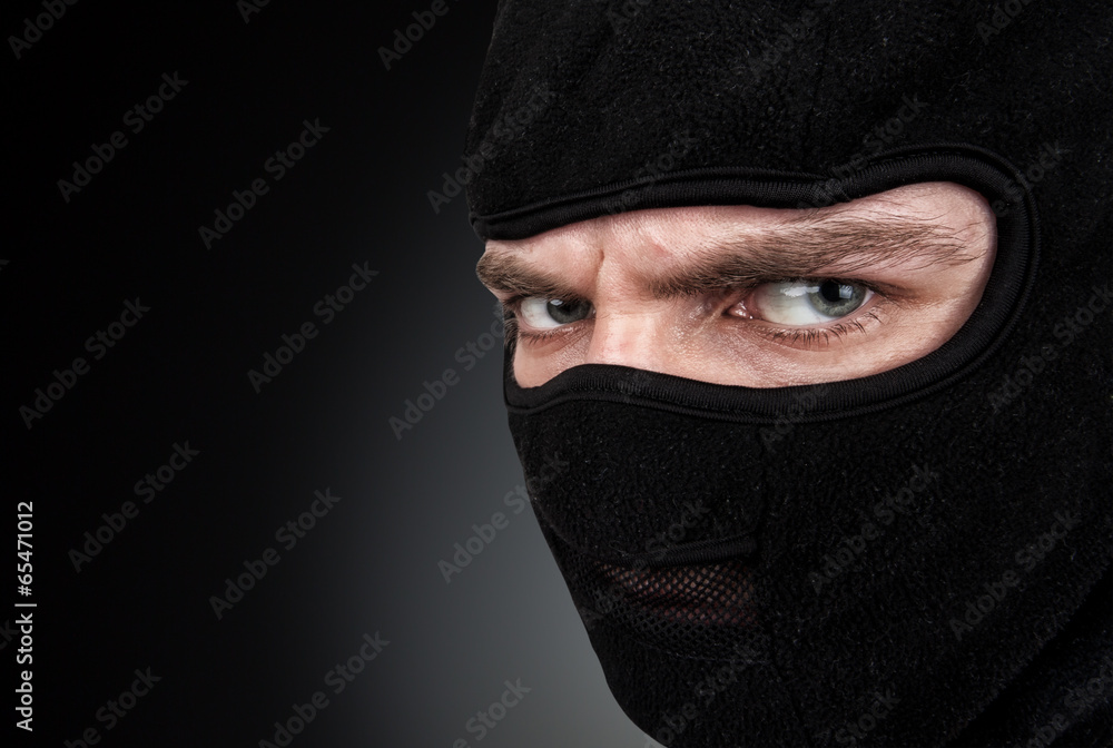 Fototapeta Man in a mask on black background